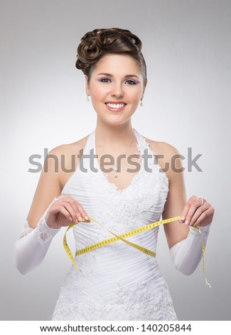 Young and beautiful bride measures her waist over the grey background - stock photo
