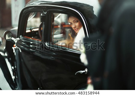 young and beautiful bride sitting in the wedding cortege
