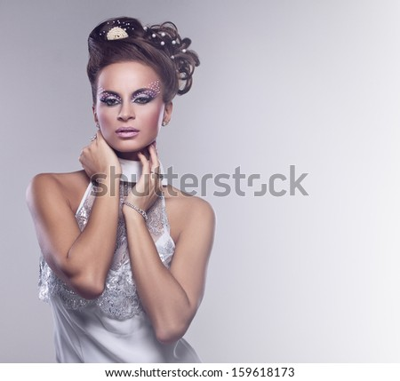 Young and beautiful bride standing in studio