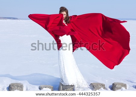 Young and beautiful bride with the red fabric playing with wind in winter background.