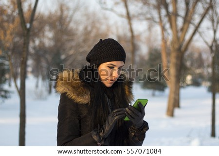 young and beautiful brunette talking to mobile phone on a snowy day
