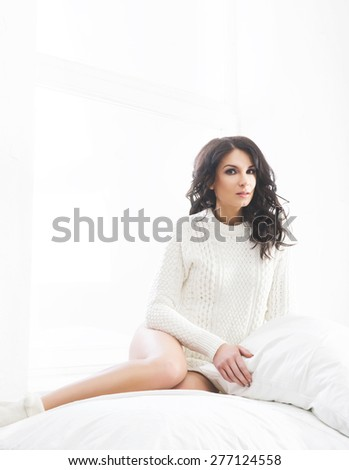Young and beautiful brunette woman posing in the bed. Morning light from the window. - stock photo