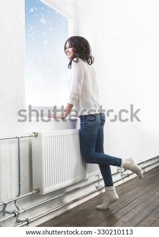 Young and beautiful brunette woman posing near the windowsill being happy about first snow.