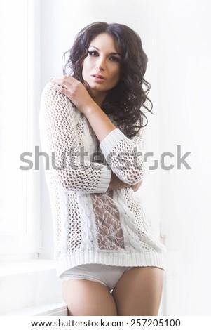Young and beautiful brunette woman posing near the windowsill. Daylight from the window. - stock photo