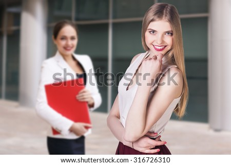 Young and beautiful business woman exploring documents in a red folder - stock photo