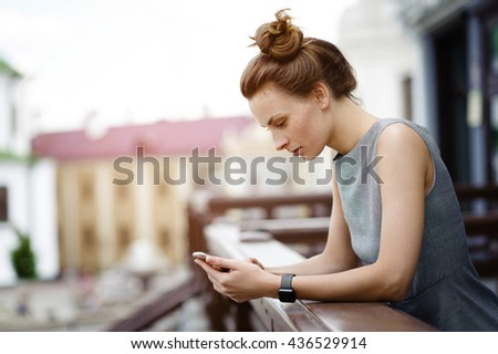 Young and beautiful business woman writes a message on his mobile phone on the street in the summer. In the hands of smart watches. - stock photo