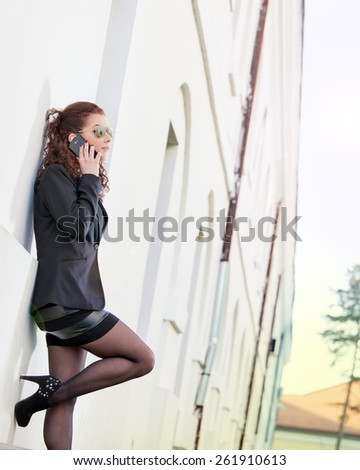 Young and beautiful businesswoman sitting on stairs with tablet. Lens flare