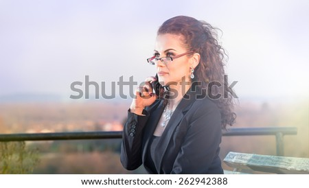 Young and beautiful businesswoman talking on cellphone outdoor. Lens flare - stock photo