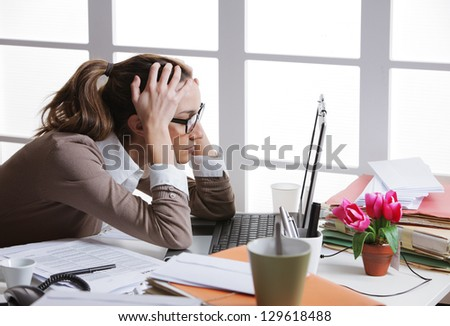 Young and beautiful businesswoman tired from work in the office.Woman holding her head - stock photo
