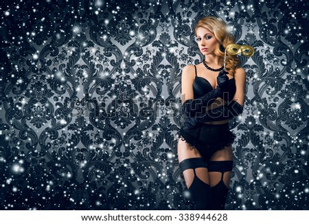 Young and beautiful cabaret dancer in sexy vintage lingerie over night snowy background. - stock photo