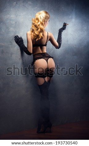 Young and beautiful cabaret dancer in sexy vintage lingerie smoking cigar over retro background - stock photo