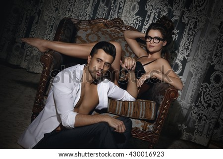Young and beautiful couple in the room with an old armchair