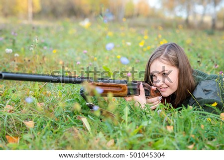 young and beautiful girl a hunter with a gun lying on the ground and aims at potential prey