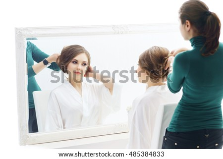Young and beautiful girl and a hairdresser preparing hairstyle. Bride doing make-up near the mirror.  Cosmetics and skin care concept.