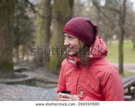 Young and beautiful girl has a rest in the Park and drinking a hot drink.