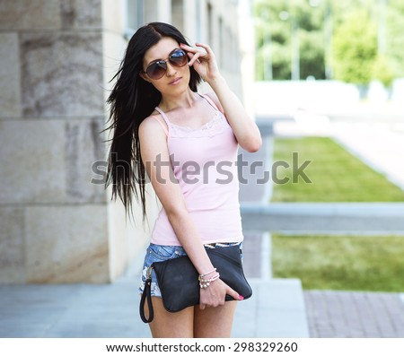 Young and beautiful girl posing near a school or institution, with glasses and a leather bag in his hand, sexy hair, in short denim shorts, fashion life style, a bright sunny day - stock photo