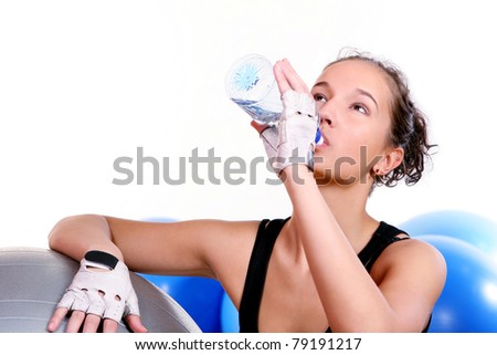 Young and beautiful girl with bottle of mineral water in gym - stock photo
