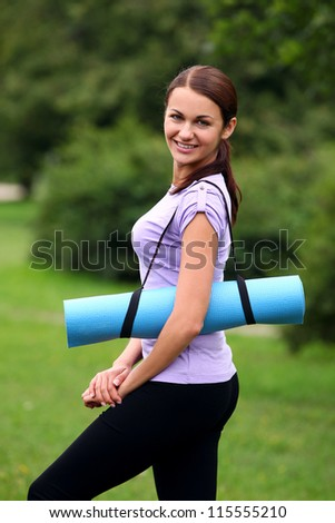 Young and beautiful girl with fitness mat in the park - stock photo