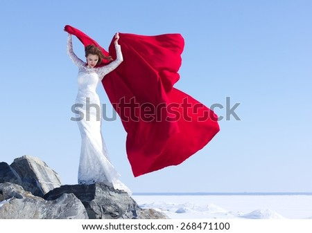Young and beautiful girl with the red fabric playing with wind in winter background. - stock photo