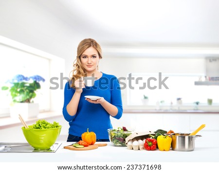 Young and beautiful housewife woman cooking in a kitchen - stock photo