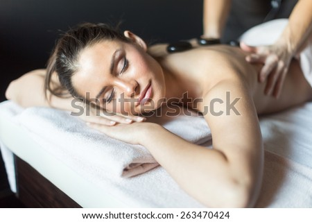 Young and beautiful lady being massaged with hot stones on her back - stock photo