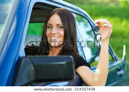 Young and beautiful lady holding car keys and posing from her blue car - stock photo