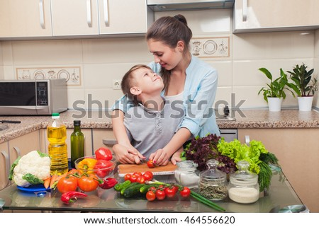 Young and beautiful mother with her son preparing a salad diet in the kitchen