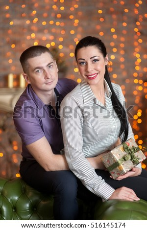 Young and beautiful pair is having fun with New Year presents in the living room. Girl is holding box with New Year presents