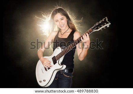 Young and beautiful rock girl dancing while playing the electric guitar