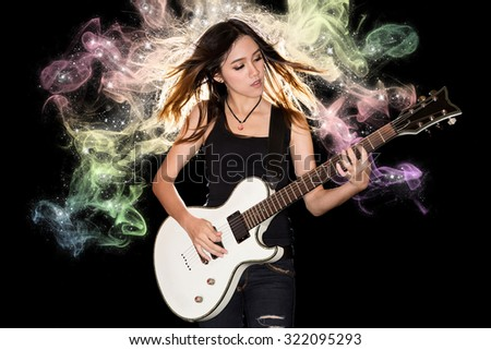 Young and beautiful rock girl playing the electric guitar with fantasy smoke and glitter star