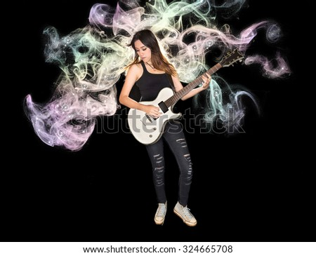 Young and beautiful rock girl playing the electric guitar with fantasy smoke and glitter star - stock photo
