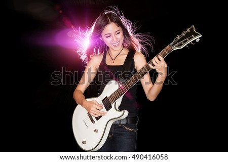 Young and beautiful rock girl smiling while playing the electric guitar