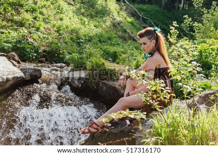 Young and beautiful savage girl near the river