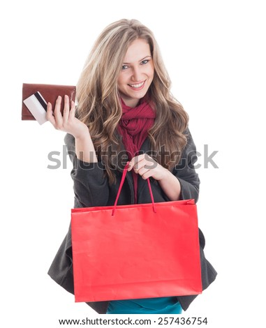 Young and beautiful shopping lady holding credit or debit card, wallet and a red shopping paper bag - stock photo
