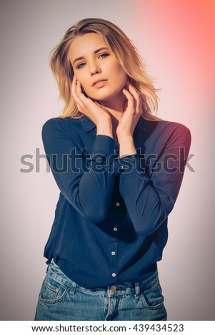 Young and beautiful. Studio shot of beautiful young woman wearing black shirt touching her face and looking at camera
