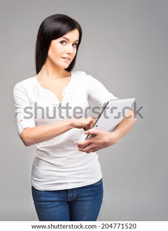 Young and beautiful teenager girl holding an ipad tablet pc in her arms over grey background - stock photo