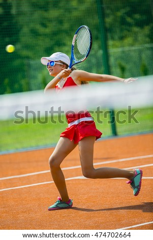 Young and beautiful tennis player in action on the court.