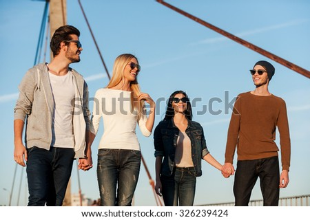 Young and beautiful. Two beautiful young couples walking outdoors together  - stock photo