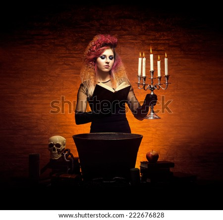 Young and beautiful witch indulging in witchcraft in a dungeon. Halloween composition. - stock photo