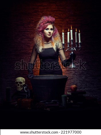 Young and beautiful witch making a witchcraft in dungeon. Halloween concept. - stock photo
