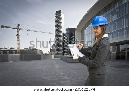 Young and beautiful woman architect holding a white board in the construction site