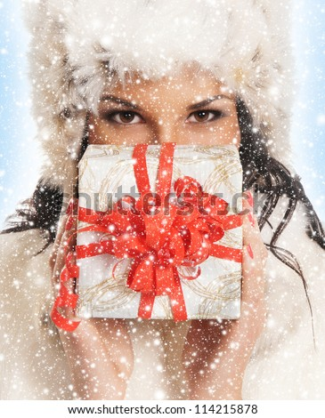 Young and beautiful woman holding a nice Christmas present - stock photo