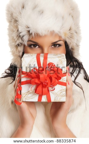 Young and beautiful woman holding a nice Christmas present over white background - stock photo
