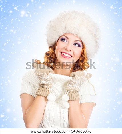Young and beautiful woman in a winter dress over Christmas background with snow. - stock photo