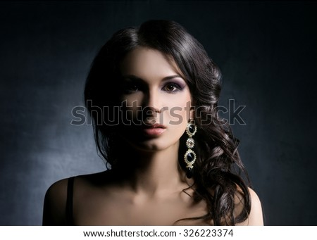 Young and beautiful  woman in jewels over dark background