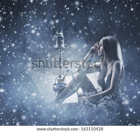 Young and beautiful woman in sexy lingerie smoking the hookah over the winter background - stock photo