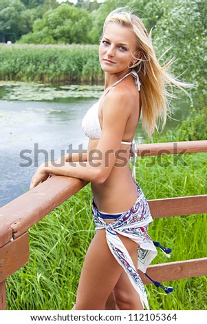 Young and beautiful woman on the pier by the forest lake - stock photo