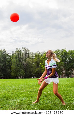 young and beautiful woman playing volleyball - stock photo