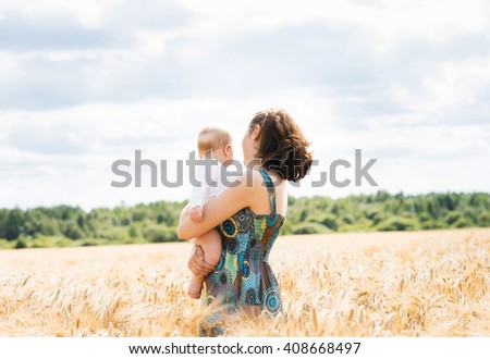 Young and beautiful woman playing with her infant baby in a meadow of wheat. Summer concept.