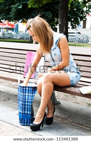 Young and beautiful woman rests with shopping in the park - stock photo